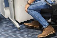 Tragende Jeans des Mannes und Stiefelschuhe sitzen auf Bürostuhl lizenzfreie stockfotos