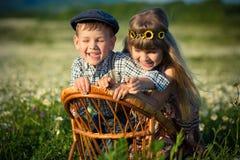 Tragende Jeans des netten hübschen Jungen und Hemd sittingand, das auf Holzstuhl zusammen mit schönem Mädchen auf Wiese der Kamil Stockfoto