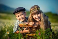 Tragende Jeans des netten hübschen Jungen und Hemd sittingand, das auf Holzstuhl zusammen mit schönem Mädchen auf Wiese der Kamil Stockfotos