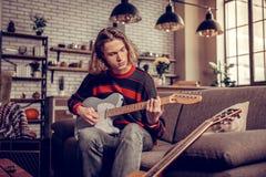 Tragende Jeans des Studenten, die Gitarre spielen und Melodie komponieren stockbilder