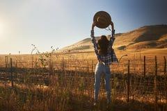 Tragende Jeans und Flanell der Frau von hinten das Betrachten von Ansicht ländlicher Kalifornien-Landschaft, die Hut in einer Luf stockfoto