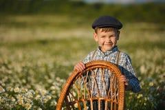 Tragende Jeans und Hemd des netten hübschen Jungen, die auf Holzstuhl auf Wiese des Kamillengänseblümchens sitzt und Sommertag he Lizenzfreies Stockbild