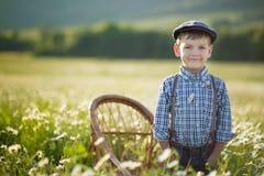 Tragende Jeans und Hemd des netten hübschen Jungen, die auf Holzstuhl auf Wiese des Kamillengänseblümchens sitzt und Sommertag he Stockbilder