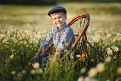 Tragende Jeans und Hemd des netten hübschen Jungen, die auf Holzstuhl auf Wiese des Kamillengänseblümchens sitzt und Sommertag he Lizenzfreie Stockfotografie
