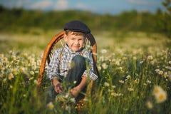 Tragende Jeans und Hemd des netten hübschen Jungen, die auf Holzstuhl auf Wiese des Kamillengänseblümchens sitzt und Sommertag he Lizenzfreies Stockfoto