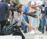 Tragende Kameraausrüstung des nicht identifizierten Frauenreporters Stockfotos