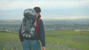 Tragende kampierende Ausstattung und Rucksack des jungen Mannes, welche die Berge, reisend betrachtet stock video