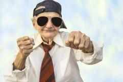 Tragende Kappe der lustigen älteren Frau in einer Kampfhaltung Stockfotos