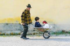 Tragende Kinder des älteren Mannes auf Schubkarre stockbild