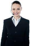 Tragende Kopfhörer der Frau, konnten Empfangsdame sein stockfotografie