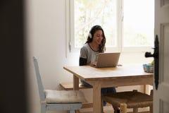 Tragende Kopfhörer der Jugendlichen, unter Verwendung des Laptops in der Küche Lizenzfreie Stockfotografie