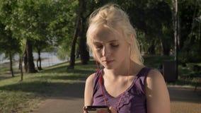 Tragende Kopfhörer der jungen Blondine und Beginnen des Laufens in Park nahe Fluss während des Morgens, lächelnd stock video footage
