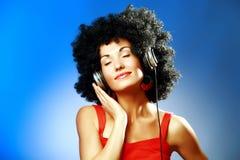 Tragende Kopfhörer der schönen Frau, welche die Musik genießen stockfoto
