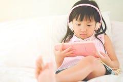 Tragende Kopfhörer des asiatischen Mädchens, die glückliche Videoclips aufpassen lizenzfreies stockfoto