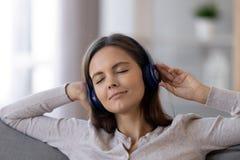 Tragende Kopfhörer des entspannten ruhigen jugendlich Mädchens, die beruhigende Musik hören stockfotos
