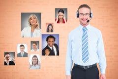 Tragende Kopfhörer des Geschäftsmannes mit den Kollegen, die verschiedene Ausdrücke zeigen Lizenzfreie Stockfotografie