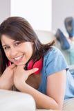 Tragende Kopfhörer des hübschen Brunette um Hals auf der Couch Lizenzfreies Stockfoto