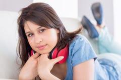 Tragende Kopfhörer des hübschen Brunette um Hals auf der Couch Stockfoto