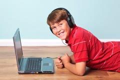 Tragende Kopfhörer des Jungen mit Laptop Lizenzfreie Stockfotos
