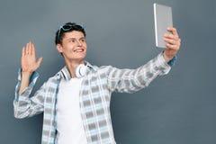 Tragende Kopfhörer des Mannes lokalisiert auf der grauen Wandtourismus-Konzeptstellung, die Videoanruf auf dem digitalen Tablette lizenzfreie stockfotos