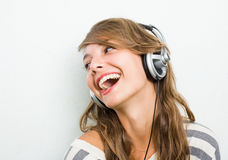 Tragende Kopfhörer des schönen Brunette, lachend. Stockfotos