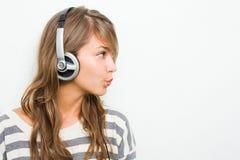 Tragende Kopfhörer des schönen Brunette, pfeifend. Stockfotografie