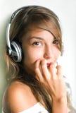 Tragende Kopfhörer des schüchternen jungen Brunette, überrascht, Stockbild