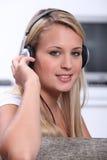 Tragende Kopfhörer einer blonden Frau Stockfotos