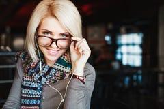 Tragende Kopfhörer und Gläser des blonden Mädchens Stockfotos