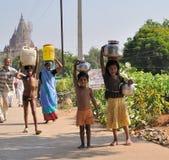 Tragende Krüge Wasser in Indien Stockbilder