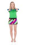 Tragende kurze Hosen des blonden Mädchens und ein T-Shirt, das mit den geraden Händen oben in der Front hält blaue Dummköpfe steh Stockfotos