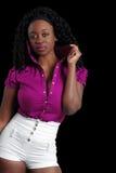Tragende Kurzschlüsse der jungen jamaikanischen Frau auf Schwarzem Stockfoto
