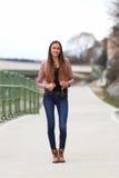 Tragende Lederjacke, Blue Jeans und Stiefel des Brunettemädchens stockbilder