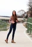 Tragende Lederjacke, Blue Jeans und Stiefel des Brunettemädchens lizenzfreie stockfotos