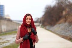 Tragende Lederjacke des Brunettemädchens mit schwarzen Handschuhen und einem roten Schal lizenzfreie stockbilder