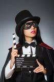 Tragende Maske der Frau mit Filmbrett Stockfotografie