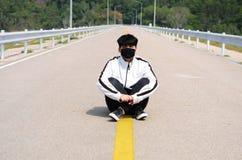 Tragende Maske des Jungen auf der Straße nachdem dem Rütteln sich entspannen stockbild