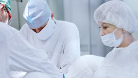 Tragende Maske des reifen Chirurgen und weiße Uniform während des Arbeitens umgeben vom medizinischen Personal stock footage