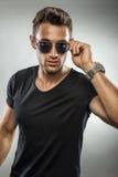 Tragende Modesonnenbrille des gutaussehenden Mannes, Sie betrachtend Stockfotos