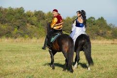 Tragende Nationalkostüme der Leute reiten zu Pferd an der Landschaft, Almaty, Kasachstan stockfoto