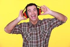 Tragende Ohrenschützer des Mannes Stockbilder