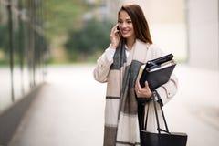 Tragende Ordner der Geschäftsfrau zu arbeiten stockbild
