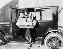 Tragende Pakete der Frau vom Auto (alle dargestellten Personen sind nicht längeres lebendes und kein Zustand existiert Lieferante Lizenzfreies Stockbild