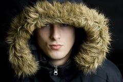 Tragende Pelzhaube des jungen stattlichen Mannes in einem Winter Stockfotografie
