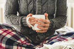 Tragende Pyjamas der jungen Frau und gemütliche wollige graue Wolljacke, die Becher Tee auf Bett halten Stockfotografie