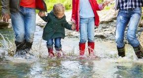 Tragende Regenstiefel der glücklichen Familie, die in einen Gebirgsfluss springen lizenzfreies stockfoto