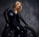 Tragende Rennläuferuniform der Schönheit, werfend in einem Studio beim Sitzen auf einem Rad und Halten eines Schutzhelms auf lizenzfreie stockbilder