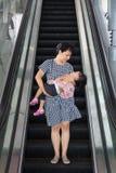 Tragende schlafende Tochter der asiatischen chinesischen Mutter, die Rolltreppe nimmt Lizenzfreies Stockfoto
