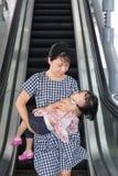 Tragende schlafende Tochter der asiatischen chinesischen Mutter, die Rolltreppe nimmt Lizenzfreie Stockfotos