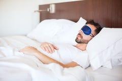 Tragende Schlafmaske des Mannes in einem Hotel Stockfotos